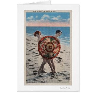 2 femmes les prenant un bain de soleil et carte