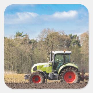 Agriculteur sur le tracteur labourant le sol sticker carré
