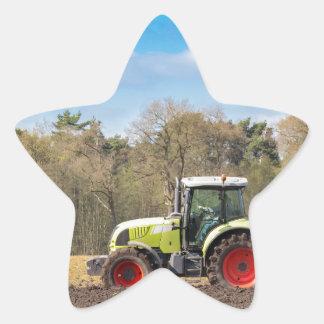 Agriculteur sur le tracteur labourant le sol sticker étoile