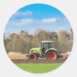 Agriculteur sur le tracteur labourant le sol sticker rond