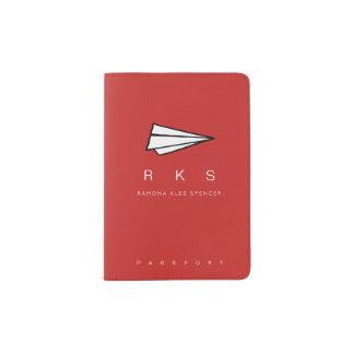 avion de papier avec le rouge de voyage de protège-passeport