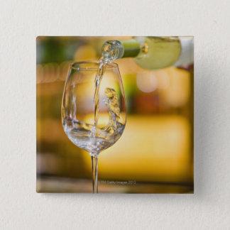 Badge Carré 5 Cm Du vin blanc est versé de la bouteille dans le