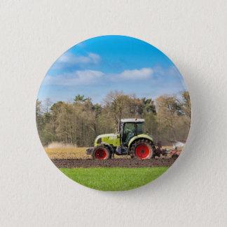 Badge Rond 5 Cm Agriculteur sur le tracteur labourant le sol