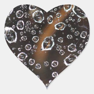 Baisses de rosée dans un filet d'araignée sticker cœur