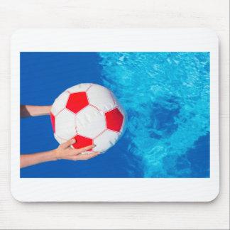 Ballon de plage de participation de bras au-dessus tapis de souris