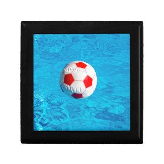 Ballon de plage flottant dans la piscine bleue boîte à bijoux