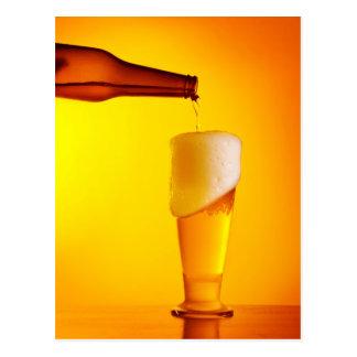Bière de versement de serveur, verre d'une boisson carte postale