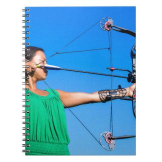Carnet Jeune femme visant la flèche de l'arc composé