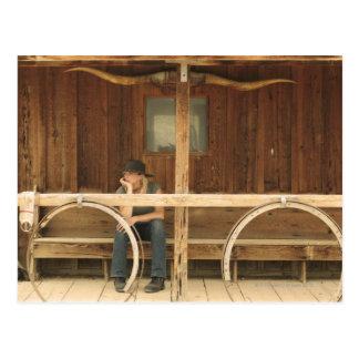 Carte Postale Cow-girl s'asseyant sur le porche de ranch