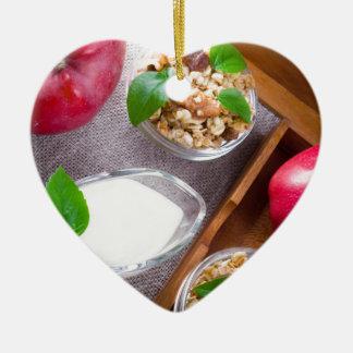 Céréale avec des noix et des raisins secs, yaourt ornement cœur en céramique