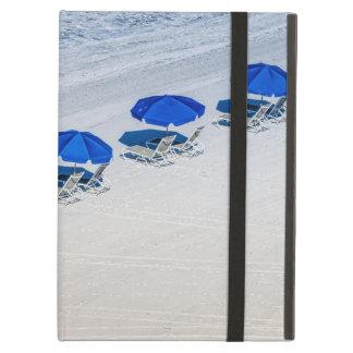Chaises de plage avec le parapluie bleu sur la protection iPad air