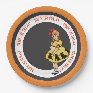 Chat noir de robe de jaune de petite fille de des assiettes en papier