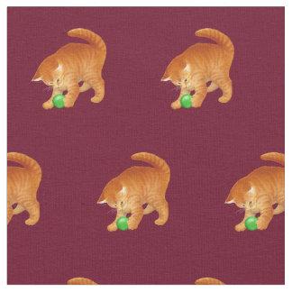 Chat orange de Kitty jouant avec le tissu de boule