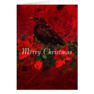 Corneille sur les poinsettias et la carte de Noël