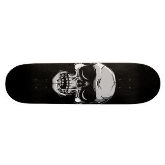 Crâne avec des lunettes de soleil sur la planche à skateboards