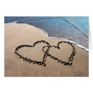 Deux coeurs dans la carte de voeux de sable