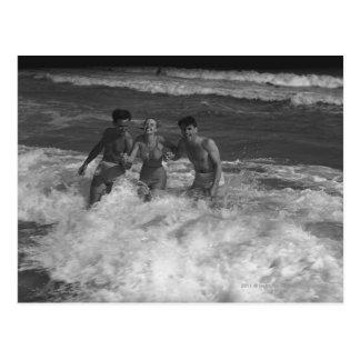 Deux jeunes hommes et femme jouant dans la vague carte postale