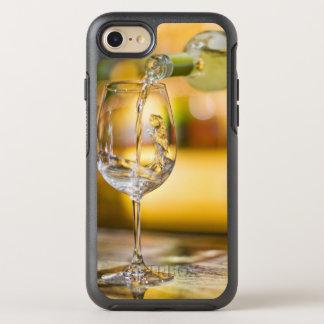 Du vin blanc est versé de la bouteille dans le coque otterbox symmetry pour iPhone 7