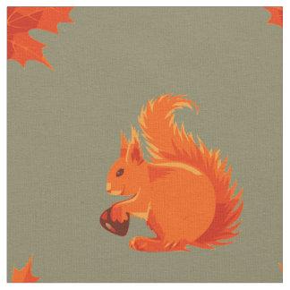 Écureuil rouge mignon avec la châtaigne et le tissu