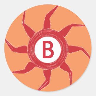 Een rood Ontwerp van de Zon op een Oranje Ronde Sticker