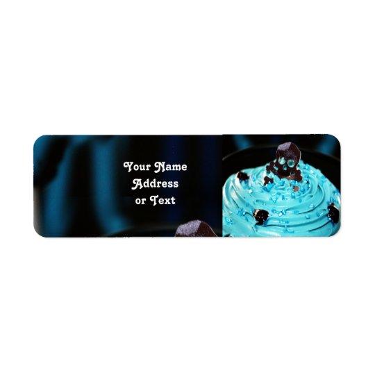 Étiquette Crâne noir de Halloween sur le petit gâteau bleu
