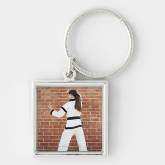 Fille faisant des arts martiaux porte-clé carré argenté