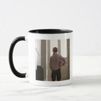 Garçon dans le foyer avec du ballon de football mug