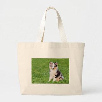Grand Tote Bag Un jeune chien de sheltie se reposant sur l'herbe