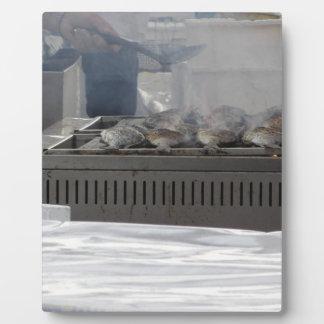 Grillant des poissons dehors plaque photo