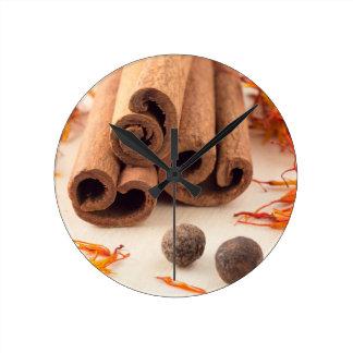 Horloge Ronde Bâtons de cannelle, safran aromatique et piment