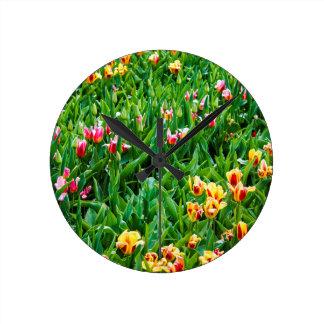 Horloge Ronde Champ avec les tulipes roses et jaunes
