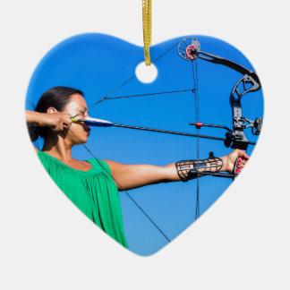Jeune femme visant la flèche de l'arc composé ornement cœur en céramique