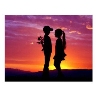 Jeune silhouette de coucher du soleil de couples carte postale