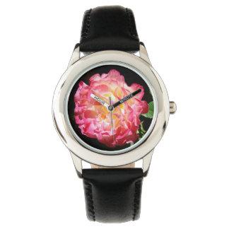 La fleur rose de l'enfant observe les cadeaux montres cadran