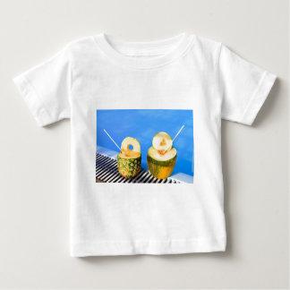 L'ananas et le melon portent des fruits avec des t-shirt pour bébé