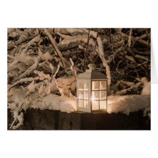 Lanterne avec une bougie au milieu de neige carte