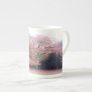 L'arbre avec le rose laisse la tasse de porcelaine