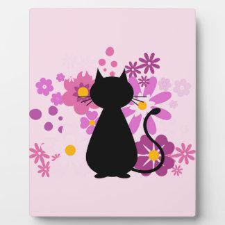 Le chat dans le rose fleurit la plaque avec le