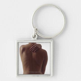 Le dos nu d'une femme avec une atteinte de main porte-clé carré argenté