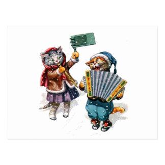 Les chats mignons jouent l'accordéon dans la neige carte postale