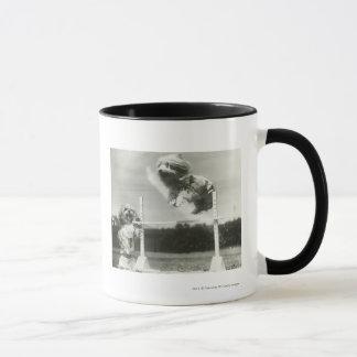 Les chiens sautant par-dessus la barre en hauteur mug