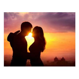 Les couples silhouettent au coucher du soleil carte postale