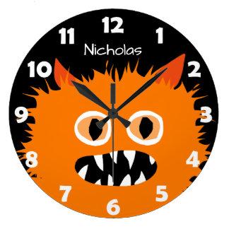 Les enfants oranges velus de monstre ont grande horloge ronde