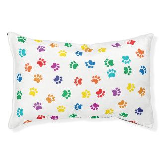 Les pattes colorées de chien poursuivent le lit