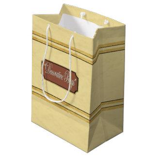 L'or crème raye le sac moyen de cadeau