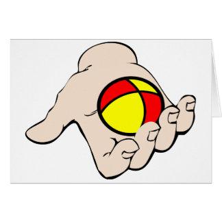 Main avec les cartes de voeux de jonglerie de
