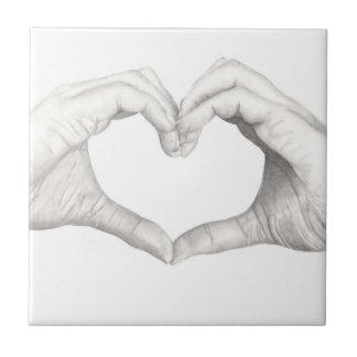 Mains dans la forme d'un coeur carreau
