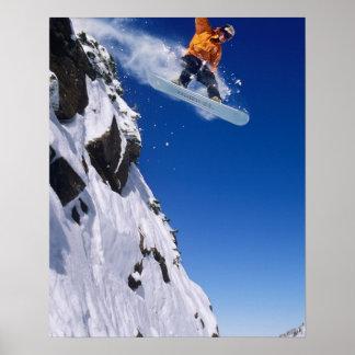 Man op een snowboard die van een kroonlijst spring plaat