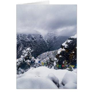 Neige, nuage et drapeaux de prière en montagnes de carte