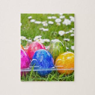 Oeufs de pâques peints colorés dans l'herbe avec puzzle